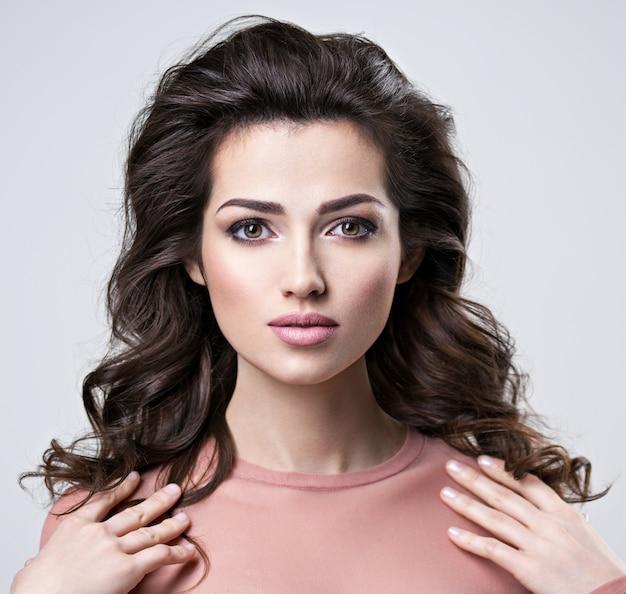Портрет женщины брюнет с красивыми длинными каштановыми волосами. довольно молодая взрослая девушка позирует в студии. крупным планом привлекательное женское лицо.