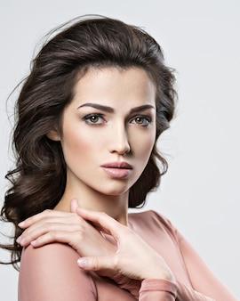 美しい長い茶色の髪を持つブルネットの女性の肖像画。クローズアップの魅力的な女性の顔をポーズするかなり若い大人の女の子。