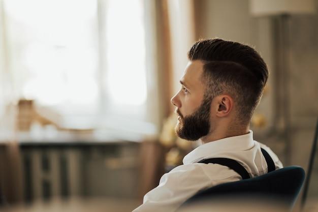Портрет жестокого бородатого мужчины в комнате. брутальный, уверенный, бородатый мужчина крупным планом.