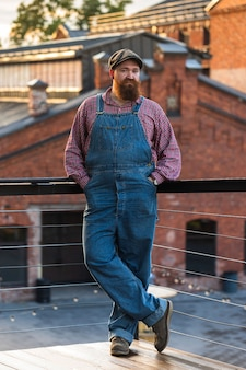 Портрет брутального бородатого мастера по ремонту мотоциклов в синем комбинезоне