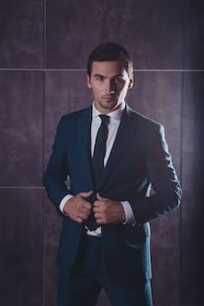 スーツに手をつないで黒いスーツの残忍なハンサムな男の肖像画
