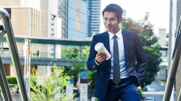 屋外の歩行者階段の通路で飲み物の紙コップとスタンドビジネスアジアの男の肖像画