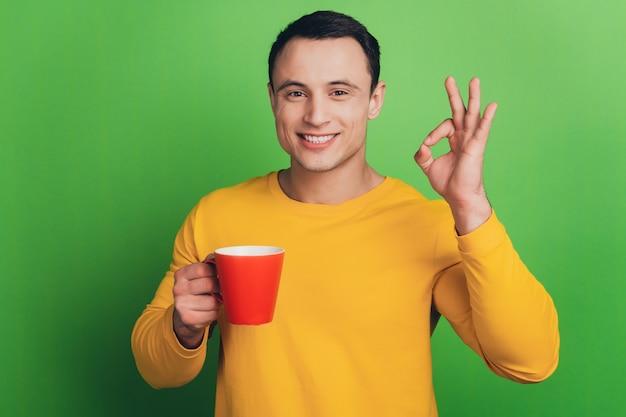 ビジネスマンの男の肖像画は、緑の背景にコーヒーショーオーケージェスチャーを飲みます