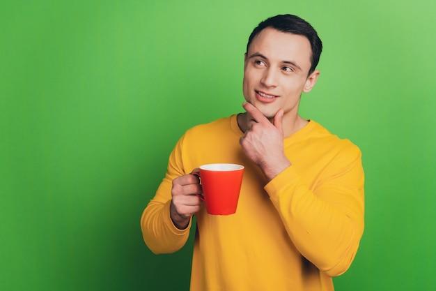 ビジネスマンの男の肖像画は、コーヒーを飲む緑の背景に空のスペースを検索すると思います