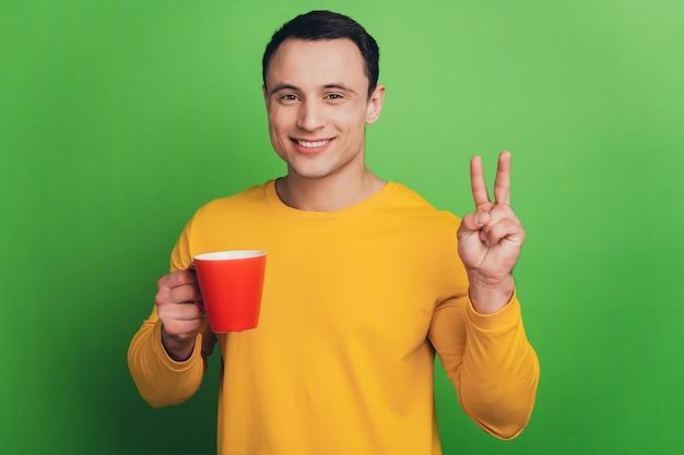 ビジネスマンの男の肖像画は、緑の背景にお茶のショーのvサインを飲みます
