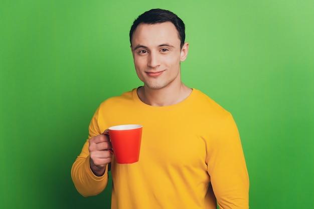 ビジネスマンの男の肖像画は緑の背景に休憩ドリンクコーヒーを作る