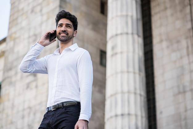 Портрет делового человека разговаривает по телефону, стоя на лестнице на открытом воздухе. концепция бизнеса и успеха.