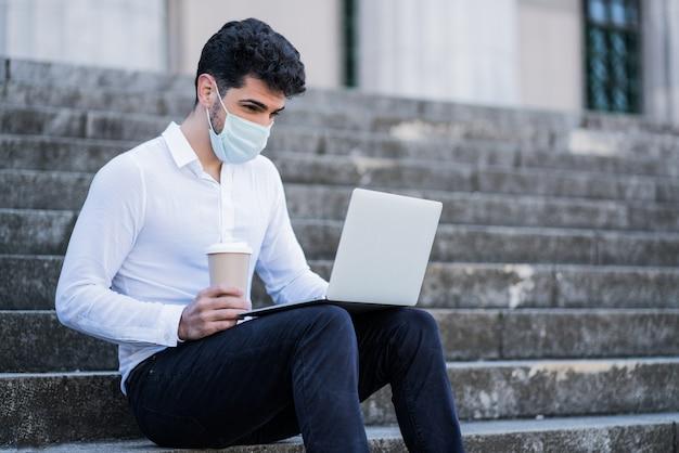 얼굴 마스크를 착용하고 야외 계단에 앉아있는 동안 자신의 노트북을 사용하는 비즈니스 남자의 초상화. 비즈니스 개념. 새로운 정상적인 라이프 스타일 개념.