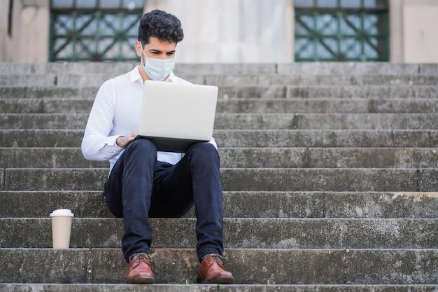 フェイスマスクを着用し、屋外の階段に座って彼のラップトップを使用してビジネスマンの肖像画