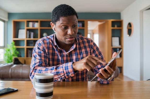 デジタルタブレットで自宅で仕事をしているビジネスマンの肖像画。ホームオフィスのコンセプト。新しい通常のライフスタイル。