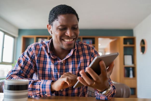 デジタルタブレットで自宅で仕事をしているビジネスマンの肖像画。