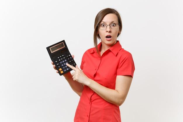 赤いシャツ、白い背景で隔離の手で電卓を保持している眼鏡のビジネス教師または会計士の女性の肖像画。高校大学での教育教育、会計カウントの概念。
