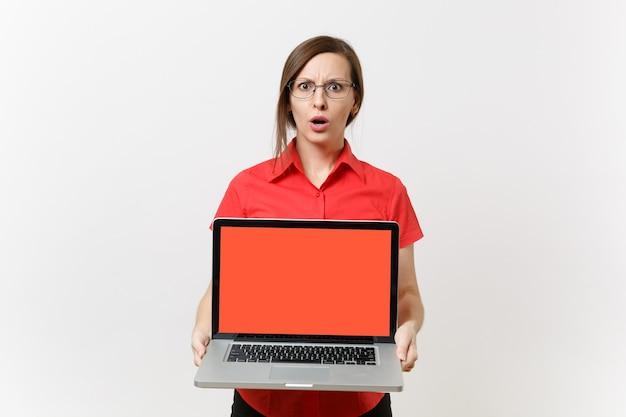 赤いシャツを着たビジネス教師の女性の肖像画は、白い背景で隔離のスペースをコピーするために空白の黒い空の画面でラップトップpcコンピューターを保持します。高校大学の概念における教育教育。