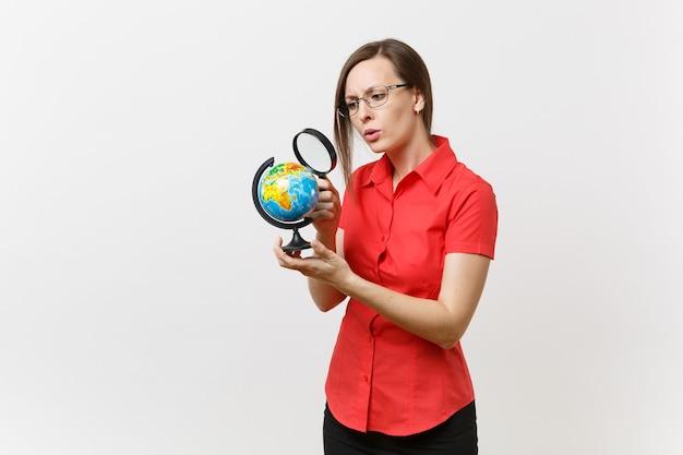 흰색 배경에 고립 된 세계에서 돋보기를 통해 찾고 빨간 셔츠에 비즈니스 교사 여자의 초상화. 고등학교 대학 개념에서 교육 교육입니다. 공간을 복사합니다.