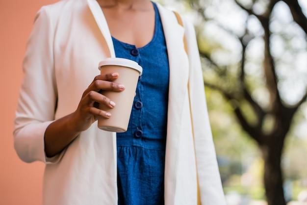 通りで屋外に立っている間コーヒーを保持しているビジネス女性の肖像画。ビジネスと都市のコンセプト。