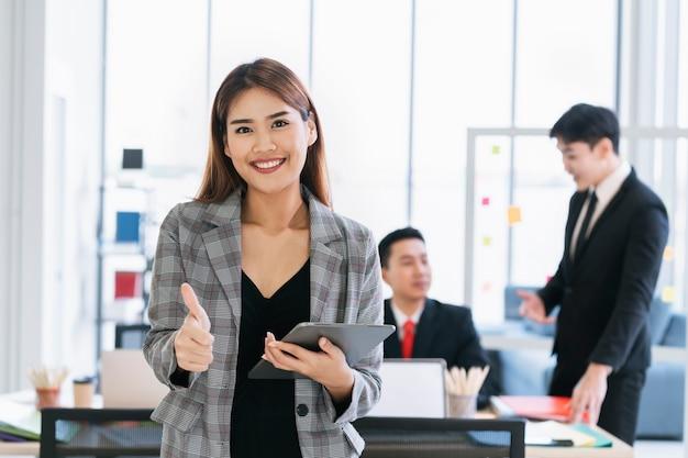 親指を立てて立って、会議室でタブレットを保持しているビジネス女性の肖像画
