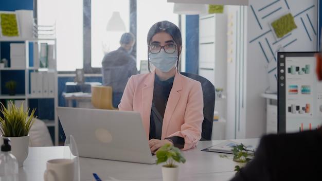 コロナウイルスのパンデミックの間にオフィスでラップトップコンピューターで作業している保護フェイスマスクを持つビジネス女性の肖像画。 covid19 virの感染を防ぐために、社会的距離を保ち続けている同僚