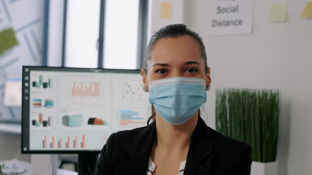 新しい通常の会社のオフィスに座っている間カメラを見て保護フェイスマスクを持つビジネス女性の肖像画。起業家はコロナウイルスの感染を防ぐために社会的距離を維持します