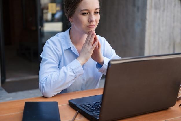 카페에 앉아서 야외에서 일하는 동안 웃고 있는 비즈니스 젊은 여성의 초상화는 메모장이 있는 노트북에서 프로젝트를 만듭니다. 고품질 사진