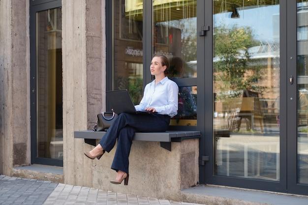 야외에서 벤치에 앉아 웃고 있는 비즈니스 젊은 여성의 초상화는 노트북에서 프로젝트를 만듭니다. 고품질 사진