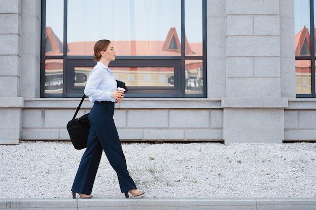 비즈니스 젊은 여성의 초상화, 노트북과 커피와 함께 도시에서 도보. 일하러 가다. 고품질 사진