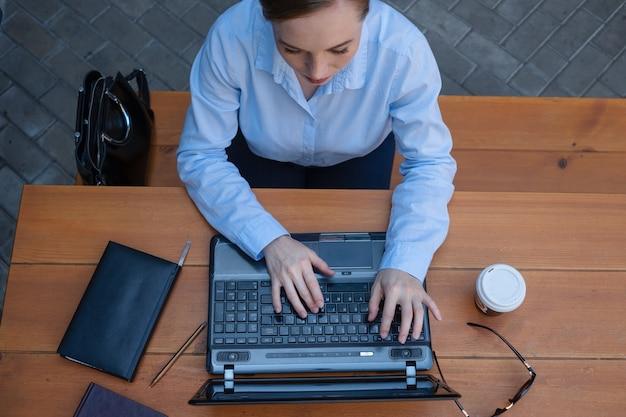 카페에 앉아서 야외에서 일하는 동안 비즈니스 젊은 여성의 초상화는 커피를 마시는 동안 메모장으로 노트북에서 프로젝트를 만듭니다. 평면도. 고품질 사진