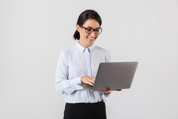 Портрет деловой женщины в очках, держащей серебряный ноутбук в офисе, изолированной над белой стеной