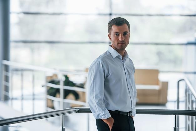 ビジネスマンの肖像画。自信のあるマネージャーがオフィスに立っています。