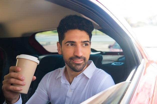 Портрет бизнесмена, пить кофе по дороге на работу в машине