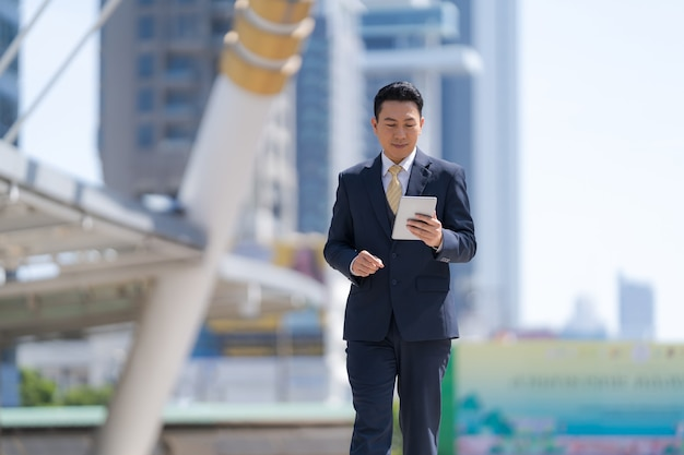 Портрет бизнесмена, держащего цифровой планшет, идущего перед современными офисными зданиями