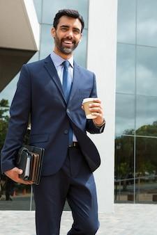 オフィスビルの近くで使い捨てカップと日記を保持しているビジネスマンの肖像画