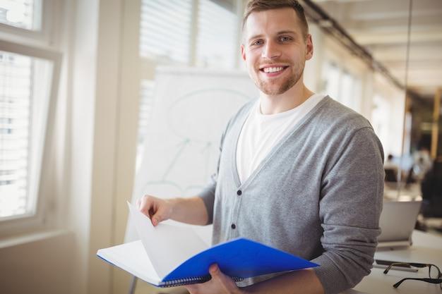 Портрет бизнесмена, держа файл в творческом офисе