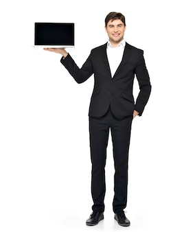 ビジネスマンの肖像画は、白で隔離の空白の黒い画面で開いたラップトップを手のひらに保持します。
