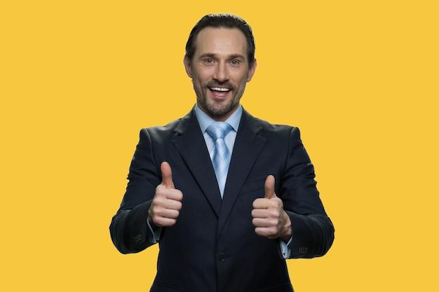 사업가의 초상화는 엄지손가락을 보여줍니다. 자신감 있는 긍정적인 고위 관리자는 승인의 표시로 제스처처럼 보이고 있습니다. 노란색 배경에 고립.