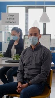 世界的大流行中のコロナウイルス感染に対する医療用フェイスマスクを着用してオフィスの机に座っているビジネスマンの肖像画。ビジネスプロジェクトで働くチームワーカーは、社会的距離を維持します