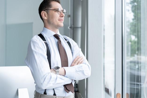 オフィスの窓際に立っているビジネスマンの肖像画。
