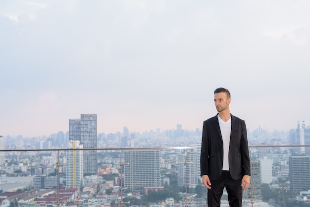 考えながらコピースペースと超高層ビルの屋上に立っているビジネスマンの肖像画