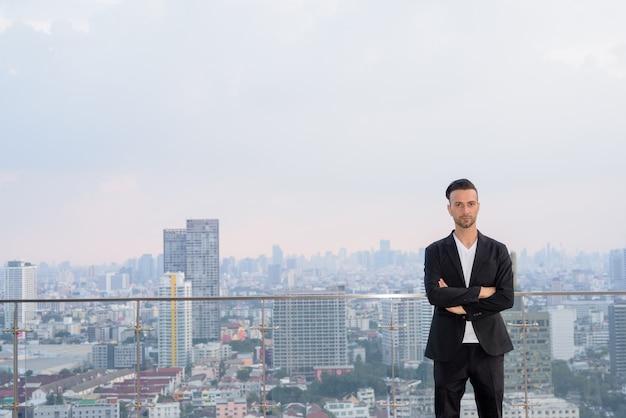 コピースペースのある超高層ビルの屋上に立っているビジネスマンの肖像画