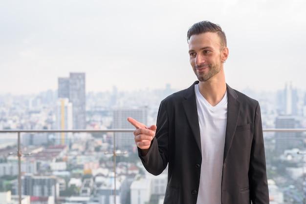 高層ビルの屋上に立っているビジネスマンの肖像画