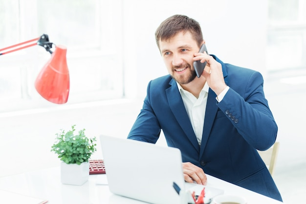 Портрет бизнесмена разговаривает по телефону в офисе