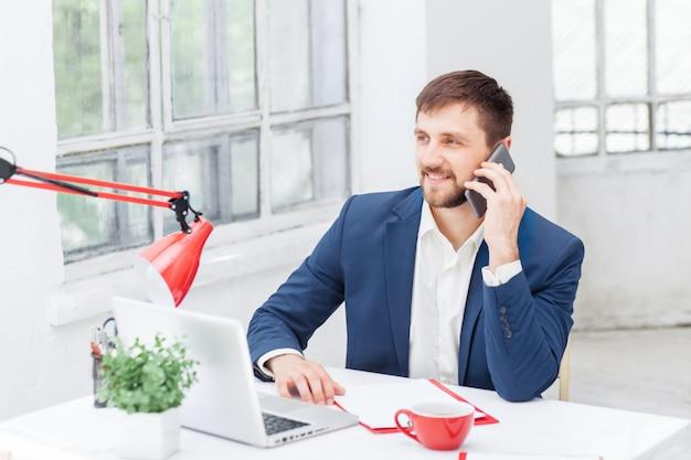 Портрет бизнесмена, разговаривает по телефону в офисе