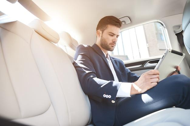 Портрет бизнесмена с помощью цифрового планшета во время путешествия