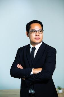 灰色の背景に眼鏡をかけているビジネスマンの肖像画。幸せな成功したビジネスマンの顔をクローズアップ
