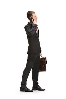 Портрет предпринимателя с портфелем на белой стене