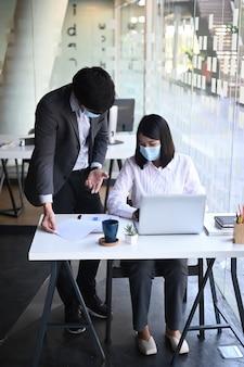 Портрет бизнесменов, носить совместную защитную маску, работая в современном офисе.