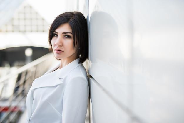 Портрет коммерсантки в современном офисе. уверенно деловая женщина со скрещенными руками стоя, прислонившись к стеклянной стене.