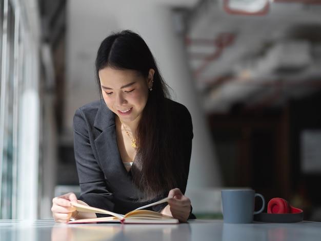 オフィスルームの白いテーブルの上の本を読んでスーツの実業家の肖像
