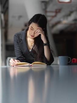 Портрет деловой женщины в костюме, читающей книгу на белом столе в офисной комнате