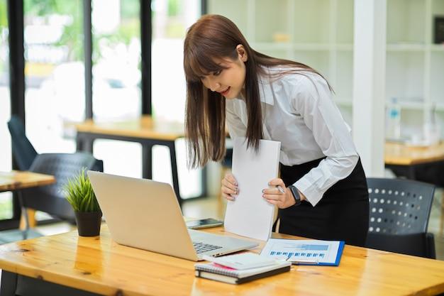 Портрет деловой женщины, готовящей документ, чтобы закончить работу стоя