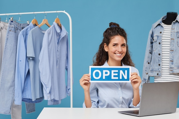 オープンプラカードとラップトップの前のテーブルに座って、彼女が洋服店で働いている笑顔の実業家の肖像画
